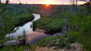 Sunset over sand dunes and river at bottom